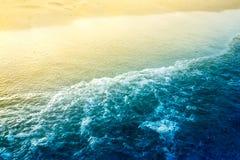 Il mare fluttua con la sabbia dorata Fotografie Stock