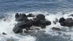 Il mare ondeggia colpire contro le grandi rocce e la rottura nella schiuma, movimento lento dell'acqua stock footage