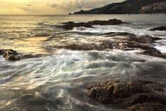 Il mare ondeggia la riga roccia della sferza di impatto sulla spiaggia Fotografia Stock