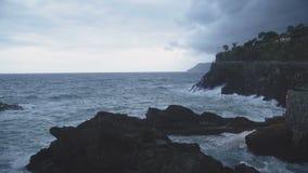 Il mare ondeggia la rottura sopra le rocce vicino al villaggio di Manarola in Italia, Cinque Terre archivi video