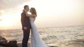 Il mare ondeggia la rottura sulle rocce durante il tramonto Lo sposo bello sta baciando la sua sposa affascinante in testa newlyw archivi video