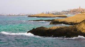 Il mare ondeggia la spruzzatura dall'isola rocciosa sul fondo di orizzonte e del cielo blu video d archivio