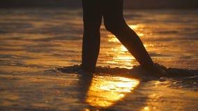 Il mare ondeggia la spruzzatura sopra i piedi femminili che camminano sulla riva al tramonto Le gambe della giovane donna che van video d archivio