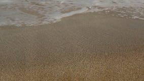 Il mare ondeggia sopra la spiaggia di sabbia video d archivio