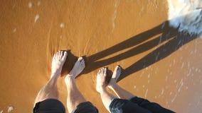 Il mare ondeggia spruzzando le gambe dell'uomo e della donna sulla spiaggia sabbiosa video d archivio