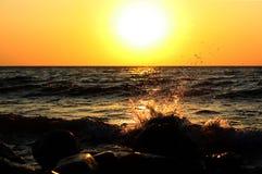 Il mare spruzza sull'alba Fotografia Stock