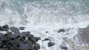 Il mare tempestoso con irrompere spumoso delle onde spruzza contro la scogliera, movimento lento archivi video