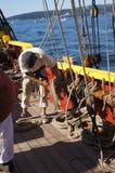 Il marinaio arrotola una riga dopo l'impostazione della vela Fotografia Stock