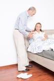 Il marito aiuta la moglie ad uscire del letto Fotografie Stock