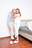 Il marito aiuta la moglie ad uscire del letto immagine stock