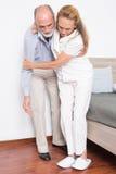 Il marito aiuta la moglie ad uscire del letto Immagine Stock Libera da Diritti