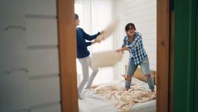 Il marito allegro e la moglie stanno divertendo con la lotta di cuscino su letto matrimoniale a casa che ridono e che si rilassan stock footage