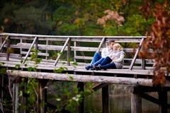 Il marito bacia la sua moglie incinta che si siede su un ponte di legno fotografia stock libera da diritti