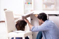 Il marito che ripara tavola tagliata a casa fotografia stock libera da diritti