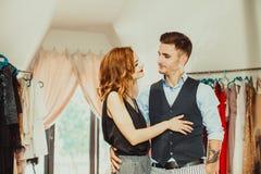 Il marito contribuisce a scegliere il vestito per la sua moglie immagini stock libere da diritti
