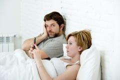 Il marito delle coppie a letto ha frustrato insoddisfatto turbato mentre moglie che per mezzo del telefono cellulare immagine stock libera da diritti