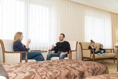 Il marito e la moglie ed i bambini nella camera di albergo I bambini stanno sedendo sul letto, genitori sulle sedie giovane fotografia stock