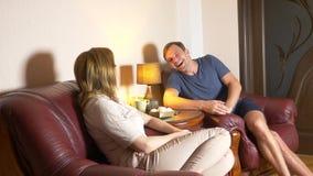 Il marito e la moglie felici delle coppie stanno sedendo a casa nel salone, parlando rilassi tardi e beva il tè alla notte fotografia stock
