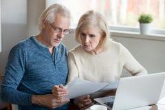 Il marito e la moglie più anziani seri hanno letto i documenti della banca a casa fotografia stock