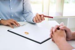 Il marito e la moglie stanno leggendo l'accordo di divorzio e la penna d'archivio a immagini stock