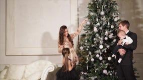 Il marito, la moglie e loro piccoli bambini decorano insieme l'albero di Natale tutto archivi video