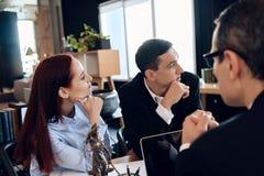 Il marito sconcertato sta sedendosi con la giovane moglie dietro la tavola del ` s dell'avvocato di divorzio fotografia stock