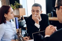 Il marito sconcertato sta sedendosi con la giovane moglie dietro la tavola del ` s dell'avvocato di divorzio immagini stock libere da diritti