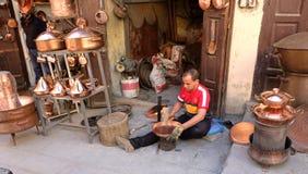 Il Marocco, la città di Fes, il 12 marzo 2019: Il fabbro del rame dello stagnaio dimostra il suo lavoro e le sue merci nella sua  immagine stock