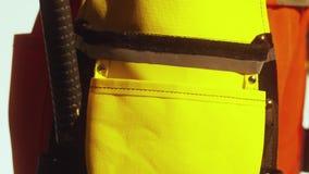 Il martello con la maniglia rossa e nera di gomma è messo nel grembiule giallo del ` s del carpentiere video d archivio