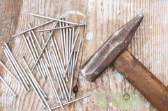 Il martello d'annata del falegname e le bullette per suole dei chiodi che si trovano sulla vecchia tavola o banco da lavoro di le Immagine Stock Libera da Diritti
