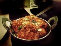 Il masala di tikka del pollo in un kadhai con il cucchiaio con burro e il coriender coprono di foglie fotografia stock