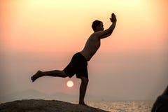 Il maschio è impegnato nell'esercizio di yoga di forma fisica sulla pietra Fotografie Stock Libere da Diritti