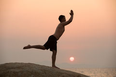 Il maschio è impegnato nell'esercizio di yoga di forma fisica sulla pietra Immagini Stock Libere da Diritti