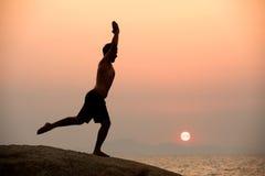 Il maschio è impegnato nell'esercizio di yoga di forma fisica sulla pietra Fotografia Stock