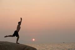 Il maschio è impegnato nell'esercizio di yoga di forma fisica sulla pietra Immagine Stock Libera da Diritti