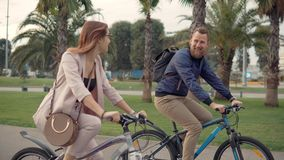 Il maschio allegro ed i ciclisti femminili stanno chiacchierando felicemente nella camminata nel parco della città archivi video