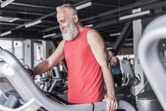 Il maschio anziano allegro sta spendendo il tempo nel centro di forma fisica Fotografie Stock