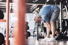 Il maschio anziano piacevole sta avendo allenamento in club atletico moderno Immagine Stock