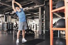 Il maschio anziano piacevole sta facendo gli esercizi nel club di sport Fotografia Stock Libera da Diritti