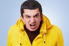 Il maschio arrabbiato furioso aggrotta le sopracciglia fronte, esamina irosamente la macchina fotografica, essendo infastidendo c fotografie stock libere da diritti