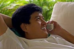 Il maschio asiatico si è disteso sul telefono con un amico Fotografia Stock Libera da Diritti
