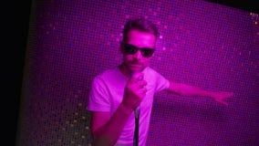 Il maschio attraente messo sugli occhiali da sole e sulla maglietta bianca canta la tenuta del microfono video d archivio