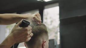 Il maschio attraente sta ottenendo un taglio di capelli moderno nel negozio di barbiere Il barbiere bagna i capelli da spruzzo e  video d archivio