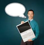 Il maschio in azzurro con il computer portatile ed i fumetti bollono Fotografia Stock