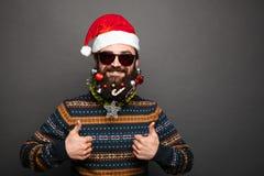 Il maschio barbuto in cappello di Santa mostra i pollici su Immagine Stock Libera da Diritti