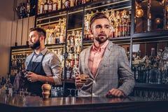 Il maschio bello alla moda in un vestito elegante tiene un vetro di whiskey al fondo del contatore della barra Fotografia Stock