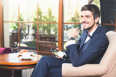 Il maschio bello ha una prima colazione francese al ristorante del caffè Immagine Stock