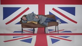 Il maschio in cappuccio e cappotto grigio si trova sul sofà e graffia nella sala con la bandiera BRITANNICA stock footage