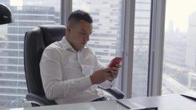 Il maschio castana bello in camicia bianca parla sullo smartphone in ufficio moderno archivi video