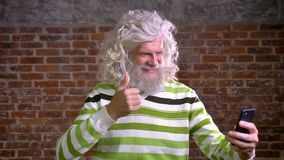 Il maschio caucasico pensionato felice con la barba spessa bianca ed i capelli lunghi sta avendo video chiamata mentre stava per  stock footage
